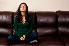 Young lady on a leather couch Stock Photo