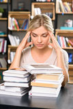 Young lady at the library looks thoroughly tired. Too much work. Nice looking girl looks tired while observing all the literature she has to look through Stock Photo