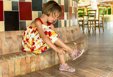 Young lady. Little girl putting on sandals Stock Photography