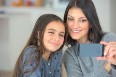 Young lady and little sister taking selfie royalty free stock images