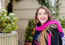 Young lady with long blonde hair and perfect makeup looking at the camera and smiling, outdoor shooting in the city Stock Images