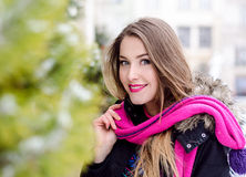 Young lady with long blonde hair and perfect makeup looking at the camera and smiling, outdoor shooting in the city Royalty Free Stock Photos