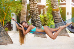 Young lady with long blonde hair relaxing in hammock on the tropical beach stock images