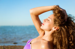 Young lady with long curly hair enjoying on the beach Stock Photos