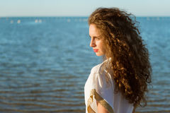 Young lady with long curly hair looking far on the beach Stock Images