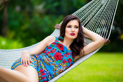 Young lady with long dark hair relaxing in hammock on the tropic Royalty Free Stock Photography