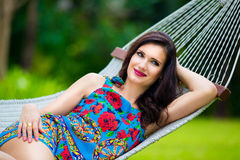 Young lady with long dark hair relaxing in hammock on the tropic Stock Images