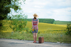Young lady looking away in the distance and. Back view of young lady standing on the road and looking away in the distance. Girl in stripped dress with straw hat Royalty Free Stock Images