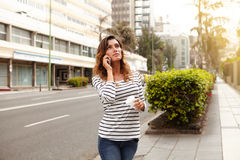 Young lady looking away while walking outdoors. Horizontal portrait of a young lady looking away while walking outdoors and talking to mobile phone Stock Photography