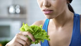 Young lady looking with disgust at green lettuce salad leaves during strong diet. Stock footage Royalty Free Stock Images
