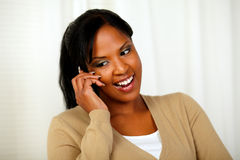Young lady looking down while talking on cellphone Royalty Free Stock Images