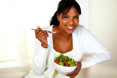 Young lady looking at you as she eats her salad Royalty Free Stock Photography