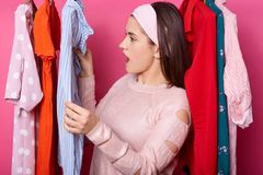Young lady looks on price tags in clothing store. Brunette girl finds stain on new blouse in showroom. Expensive clothes. Woman. Looks for dress. Caucasian royalty free stock images