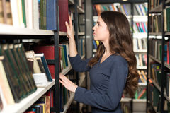 Young lady with loose long dark hair choosing a book between she Stock Images