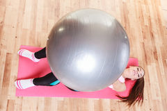 Young lady lying on the mat with fit ball. Stock Images