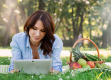 Young lady lying on a mat in the park browsing her tablet Stock Photo