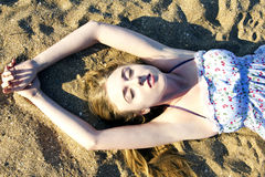 Young lady lying on the sand Royalty Free Stock Photos