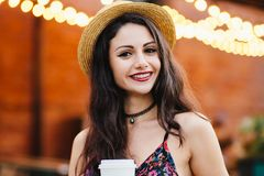 Young lady with make-up, wearing straw hat, necklace and dress, holding paper cup with coffee, smiling pleasantly at camera while. Posing at restaurant. Woman royalty free stock photo