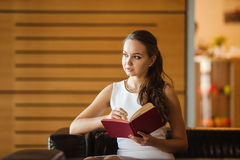 Young lady making notes in red diary. Woman in white dress planning Royalty Free Stock Photos