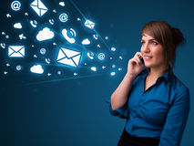 Young lady making phone call with message icons. Young lady standing and making phone call with message icons Royalty Free Stock Photo