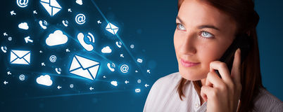 Young lady making phone call with message icons. Young lady standing and making phone call with message icons Stock Photography