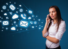 Young lady making phone call with message icons. Young lady standing and making phone call with message icons Royalty Free Stock Photography
