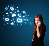 Young lady making phone call with message icons. Young lady standing and making phone call with message icons Royalty Free Stock Photos
