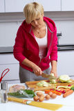 Young lady making salad in kitchen Royalty Free Stock Images