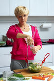 Young lady making salad in kitchen Stock Photo