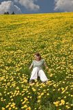 Young lady in the meadow full of flowers Stock Images