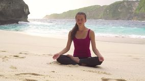 Meditating in lotus position, doing yoga exercises in morning on beach royalty free stock images