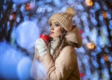 A young lady in mittens and a hat on a background of bokeh from Christmas garlands