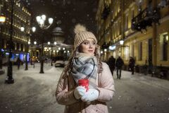 A young lady in mittens and a hat on a winter night under the lights