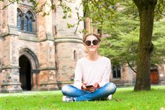 Young lady with mobile phone sitting in Glasgow University garde. Young lady with mobile phone sitting on the grass in Glasgow University garden looking at Royalty Free Stock Images