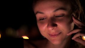 Young lady with natural makeup and eyelashes sits at night stock footage