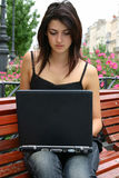 Young lady with notebook. A young lady with a laptop sit on a bench royalty free stock photography