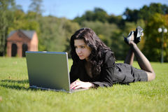 Young lady with a notebook in a park. Beautiful young lady with a notebook in a park Royalty Free Stock Photography