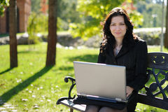 Young lady with a notebook in a park. Beautiful young lady with a notebook in a park Stock Photos