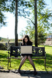 Young lady with a notebook in a park. Beautiful young lady with a notebook in a park Stock Images