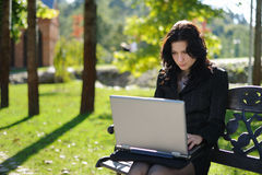 Young lady with a notebook in a park. Beautiful young lady with a notebook in a park Stock Image