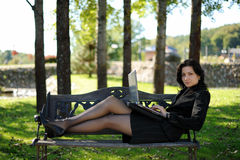 Young lady with a notebook in a park. Beautiful young lady with a notebook in a park Stock Photography