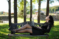 Young lady with a notebook in a park. Beautiful young lady with a notebook in a park Royalty Free Stock Image