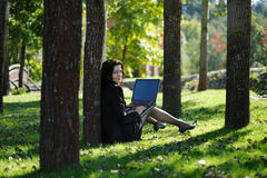 Young lady with a notebook in a park. Beautiful young lady with a notebook in a park Royalty Free Stock Photo
