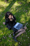 Young lady with a notebook in a park. Beautiful young lady with a notebook in a park Royalty Free Stock Images