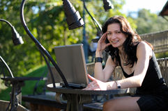 Young lady with a notebook in a summer cafe. Beautiful young lady with a notebook in a summer cafe Stock Photography