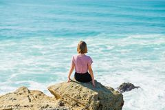 Young lady and ocean. Girl looks at the stormy ocean sitting on a rock stock photo