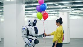 Young lady is offering colourful balloons to a cyborg stock video