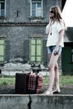 Young lady on an old railway station. Young lady phone on the platform with old fashioned suitcases Stock Photos