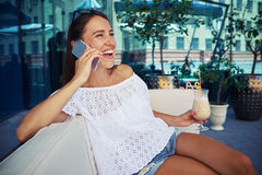 Young lady in open air café drinking cocktail and talking on th Royalty Free Stock Photography