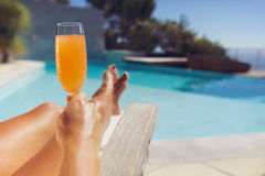 Young lady with orange juice sunbathing at the poolside Stock Photo